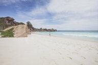 Seychelles, La Digue, Grand Anse, woman walking at the beach - MMAF00686