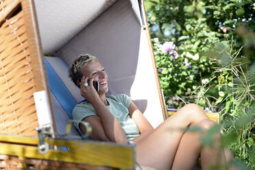 Laughing woman on the phone sitting on hooded beach chair in the garden - BFRF01923