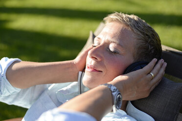 Portrait of woman listening music with headphones in the garden - BFRF01929