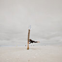 Surreal shot of a man balancing off a beach sign at sea under a cloudy sky - INGF04577