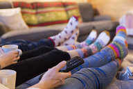 Family in colorful socks relaxing, watching TV in living room - HOXF03954