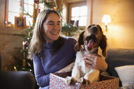 Happy teenage girl with yawning dog in Christmas gift box - HOXF03957