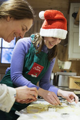 Mother and daughter in Christmas apron and Santa hat baking in kitchen - HOXF03963