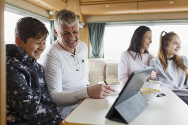 Family relaxing, eating breakfast and using digital tablet in motor home - HOXF03972