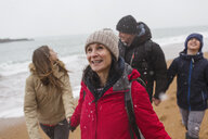 Snow falling over happy family on winter beach - HOXF03984
