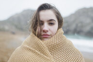 Portrait confident, serious girl with snow in hair wrapped in blanket on winter beach - HOXF03990