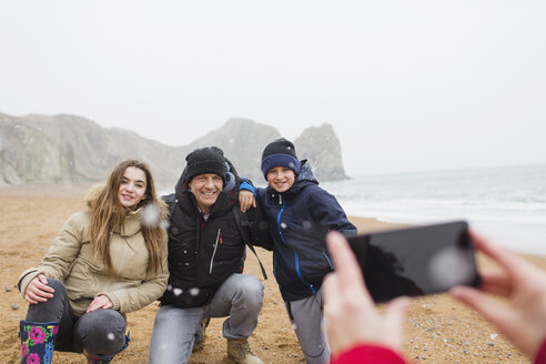 Happy family posing for photograph on snowy winter beach - HOXF04008