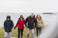 Family in warm clothing on cliff overlooking ocean - HOXF04017