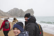 Portrait father and son in warm clothing walking on snowy winter ocean beach - HOXF04026