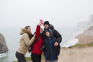 Family with camera phone taking selfie on cliff overlooking ocean - HOXF04029
