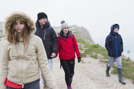 Family in warm clothing walking on snowy winter cliff path - HOXF04038