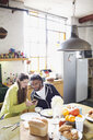 Young couple with smart phone enjoying breakfast in apartment kitchen - HOXF04062