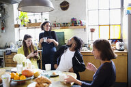 Young adult roommate friends talking at breakfast table in apartment - HOXF04077