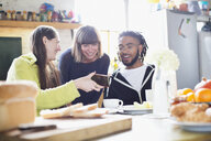 Young roommate friends using smart phone at breakfast table in apartment - HOXF04086