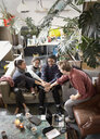 Young adult roommate friends connecting hands in huddle in apartment living room - HOXF04125