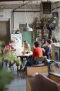 Young college student roommates studying at kitchen table in apartment - HOXF04131