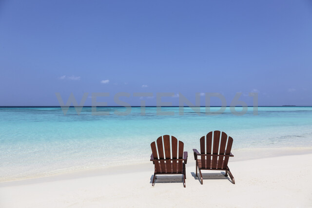 Two adirondack chairs on sunny, tranquil beach overlooking blue ocean, Maldives, Indian Ocean - HOXF04161 - Martin Barraud/Westend61