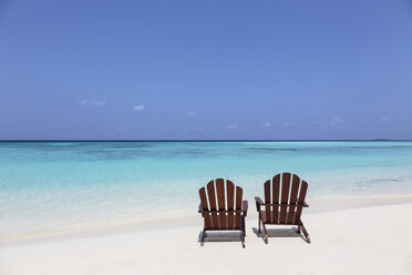 Two adirondack chairs on sunny, tranquil beach overlooking blue ocean, Maldives, Indian Ocean - HOXF04161