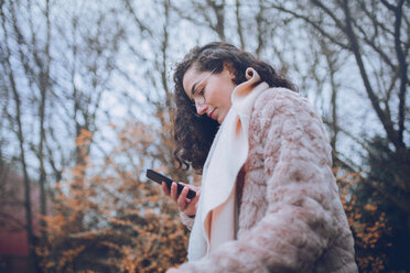 Young stylish woman looking at her mobile phone - INGF05164