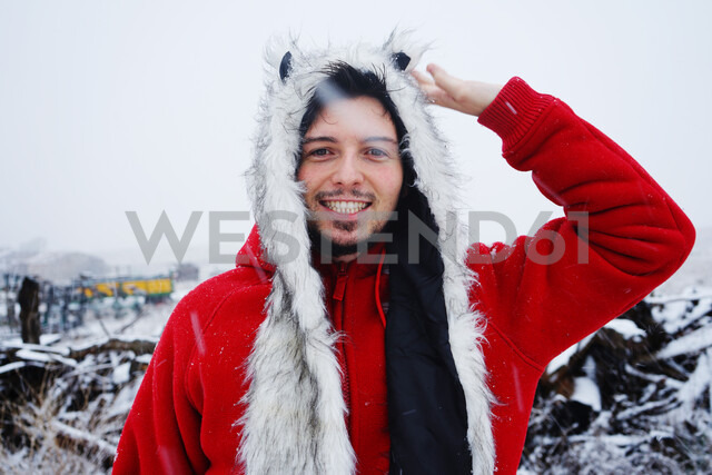 Happy man looking into the camera on a snowy day in winter - INGF05206