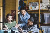 Female teacher assisting high school teenage students preparing robot on desk in classroom - MASF09294