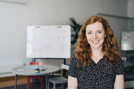 Portrait of confident redhead businesswoman standing at creative office - MASF09333