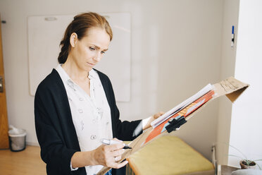 Confident businesswoman writing strategy on placard at creative office - MASF09342