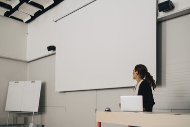 Businesswoman giving presentation while looking at blank projection screen at creative office - MASF09345