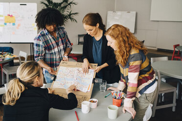 Multi-ethnic students showing map on placard to female manager at table in creative office - MASF09351