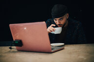 Confident young male hacker drinking coffee while looking at laptop on desk in office - MASF09369