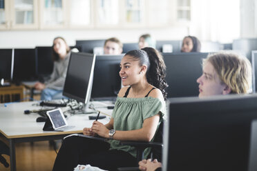 Smiling teenage girl sitting by young friend amidst computers at lab in high school - MASF09462