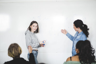 Mature teacher assisting teenage student while standing by whiteboard in classroom - MASF09465