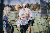 Senior male and female friends with rackets and bag talking while standing at tennis court - MASF09477