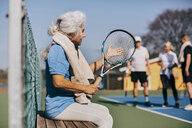 Senior woman holding tennis racket while sitting on bench at tennis court - MASF09480