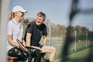 Happy senior man and woman talking while sitting on bench at tennis court - MASF09489