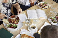 High angle view of friends having food at table in book club - MASF09492