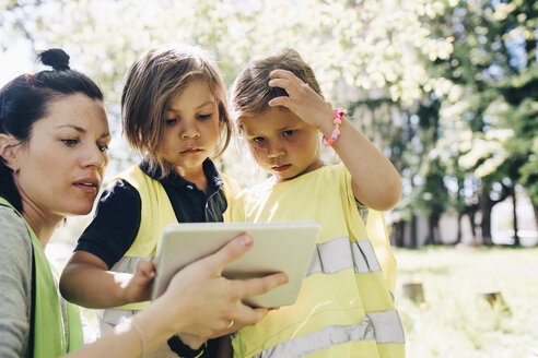 Female teacher sharing digital tablet to students in playground - MASF09522