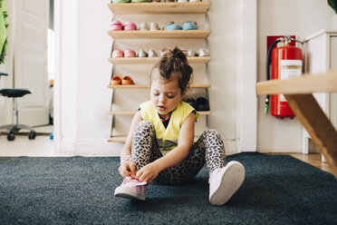 Girl sitting on carpet wearing shoes against rack in cloakroom at child care - MASF09531