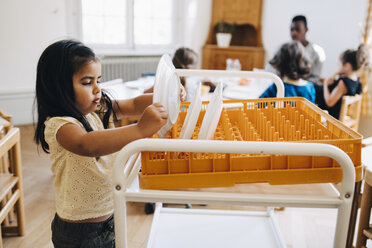Side view of girl placing plate in crate on cart in classroom - MASF09552