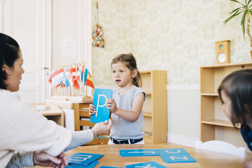 Teacher looking at girl holding letter P in classroom - MASF09567