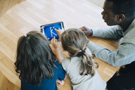 High angle view of girl touching letter K on digital tablet amidst friend and teacher at table in classroom - MASF09573