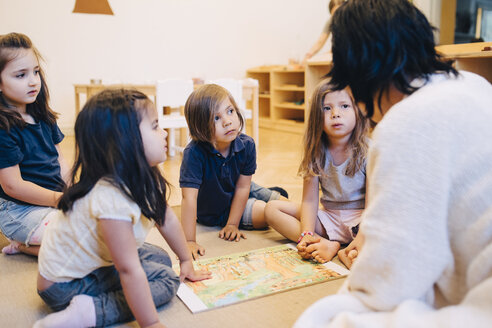 Female teacher telling story to students sitting in classroom at child care - MASF09585