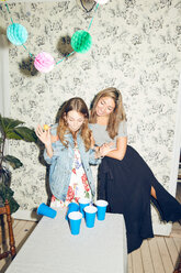 Cheerful young female friends playing beer pong during dinner party at home - MASF09594
