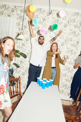 Happy young man with arms raised and female friends standing at dinner party - MASF09597