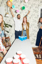 Cheerful young man standing with arms raised by female friend at dinner party - MASF09600