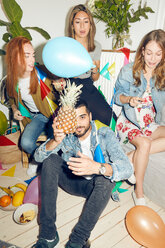 Portrait of young man holding pineapple while sitting against female friends enjoying party at home - MASF09606