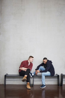 Full length of happy male students with technologies sitting on bench against wall in university - MASF09633