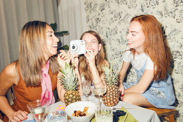 Cheerful young woman holding camera while sitting amidst female friends at home during dinner party - MASF09684