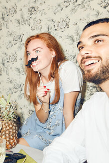 Smiling redhead woman holding mustache prop while sitting by male friend during party at home - MASF09687