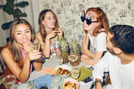 Young multi-ethnic friends celebrating at dining table during party in apartment - MASF09690